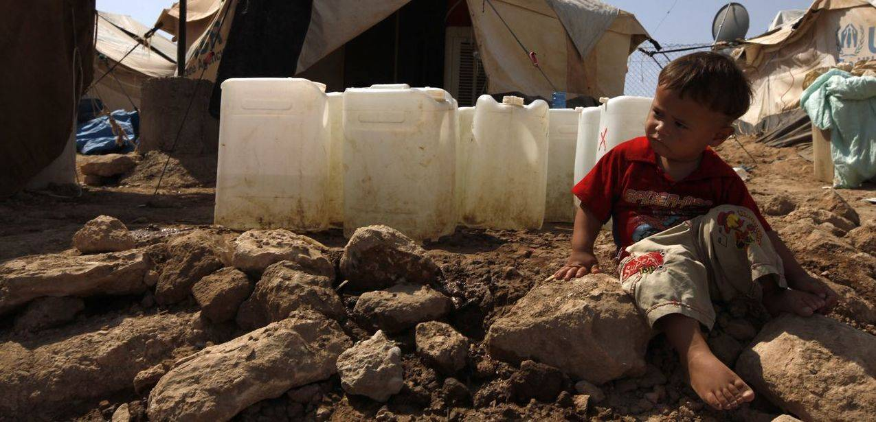 A Syrian refugee boy sits on the ground at the Domiz refugee camp in the northern Iraqi province of Dohuk