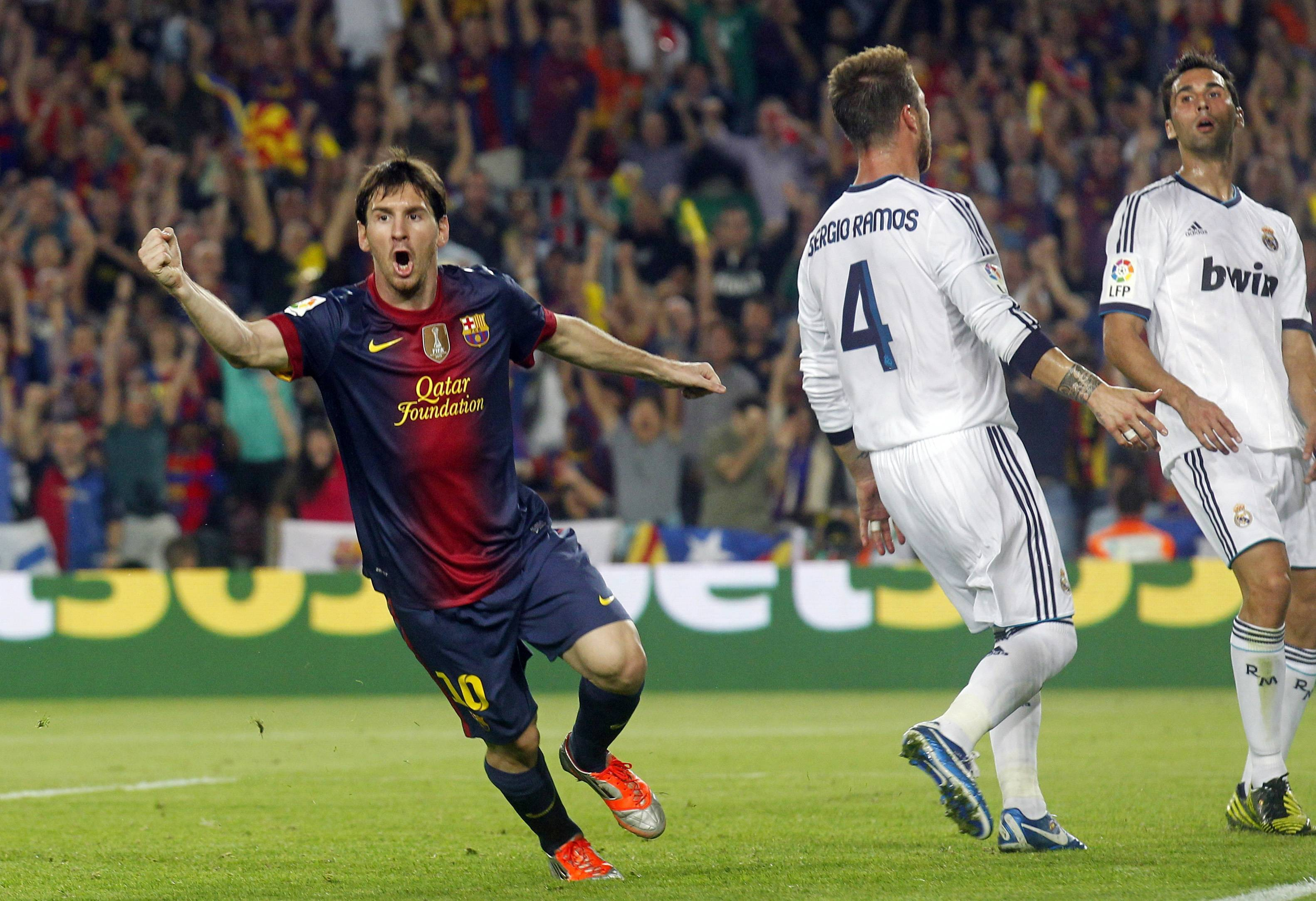 Barcelona's Lionel Messi (L) celebrates next to Real Madrid's Sergio Ramos and Alvaro Arbeloa (R) after scoring a goal during their Spanish first division soccer match at Nou Camp stadium in Barcelona, October 7, 2012.   REUTERS/Albert Gea (SPAIN - Tags: SPORT SOCCER)
