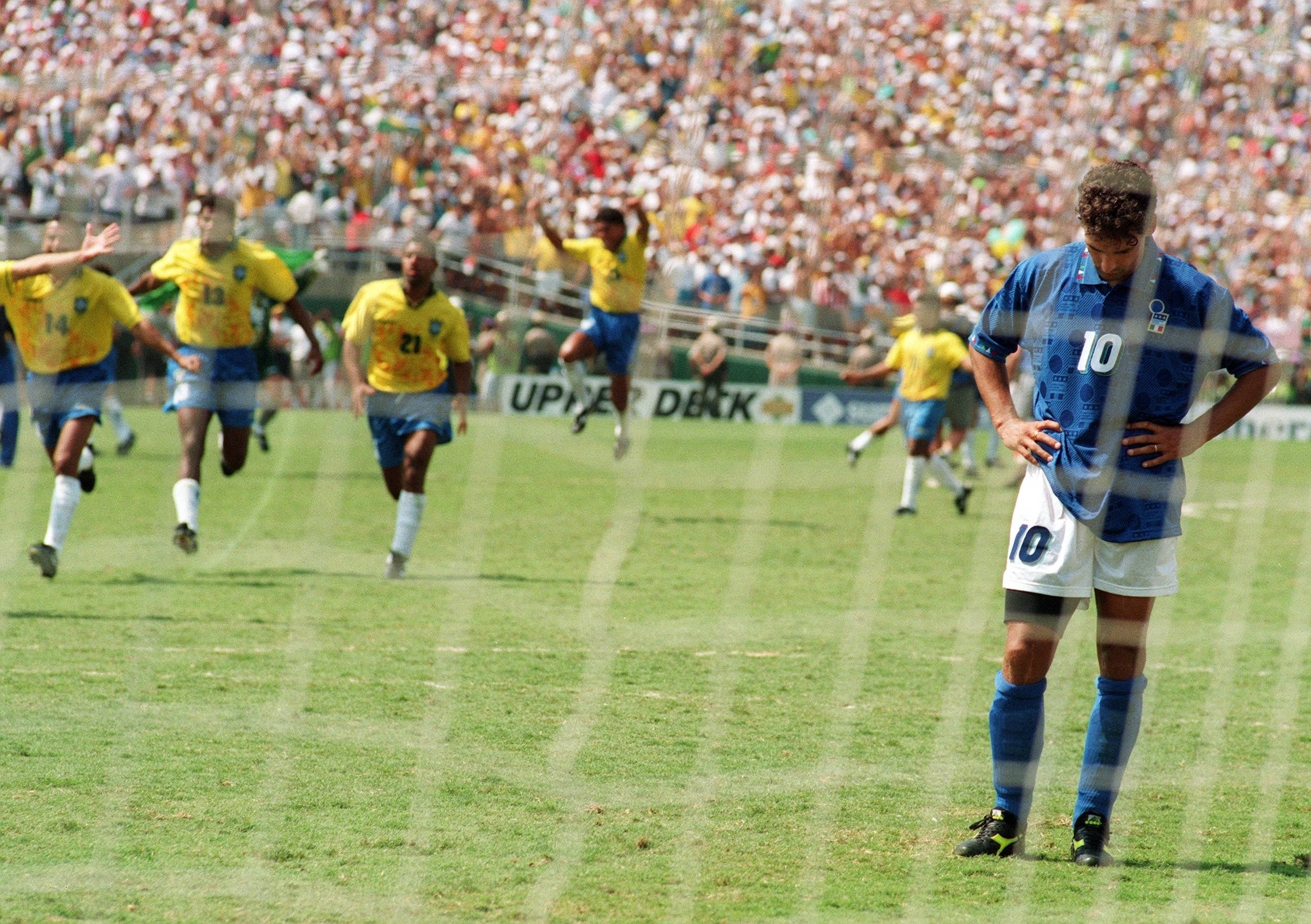 LOS ANGELES, UNITED STATES:  Brazilian players run to join their teammates as Italian midfielder Roberto Baggio bows his head after he missed his penalty kick giving Brazil a 3-2 victory in the shoot-out session (0-0 after extra time) at the end of the World Cup final, 17 July 1994 at the Rose Bowl in Pasadena. Brazil won its fourth World Cup title after 1958, 1962 and 1970.   AFP PHOTO/OMAR TORRES (Photo credit should read OMAR TORRES/AFP/Getty Images)