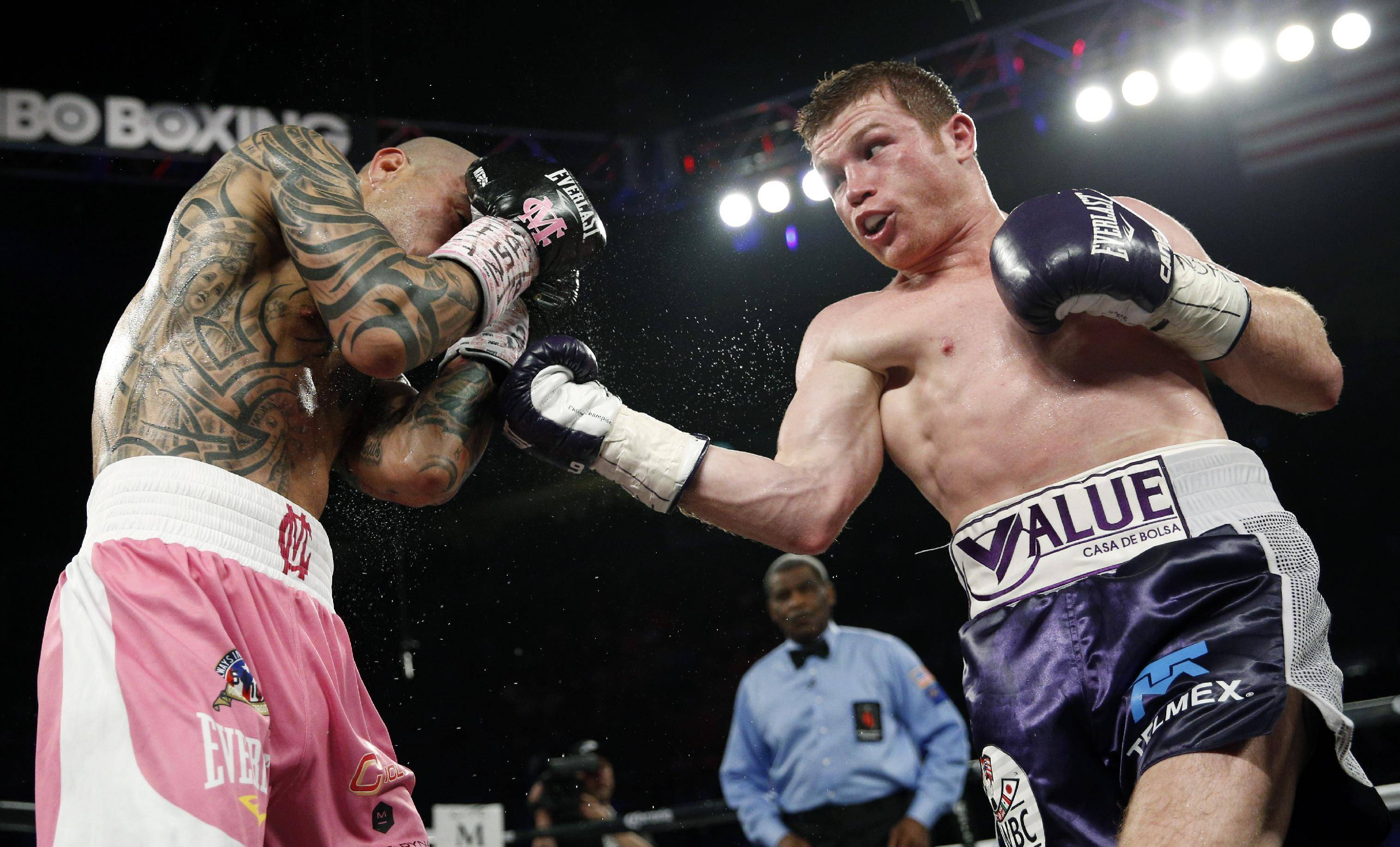 Miguel Cotto, left, of Puerto Rico, and Canelo Alvarez, of Mexico, fight each other during a WBC middleweight title bout Saturday, Nov. 21, 2015, in Las Vegas. (AP Photo/John Locher)