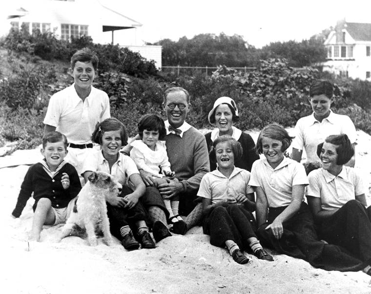 "PC 8 The Kennedy Family at Hyannis Port, 1931. L-R: Robert Kennedy, John F. Kennedy, Eunice Kennedy, Jean Kennedy (on lap of) Joseph P. Kennedy Sr., Rose Fitzgerald Kennedy (behind) Patricia Kennedy, Kathleen Kennedy, Joseph P. Kennedy Jr. (behind) Rosemary Kennedy. Dog in foreground is ""Buddy"". Photograph by Richard Sears in the John F. Kennedy Presidential Library and Museum, Boston."