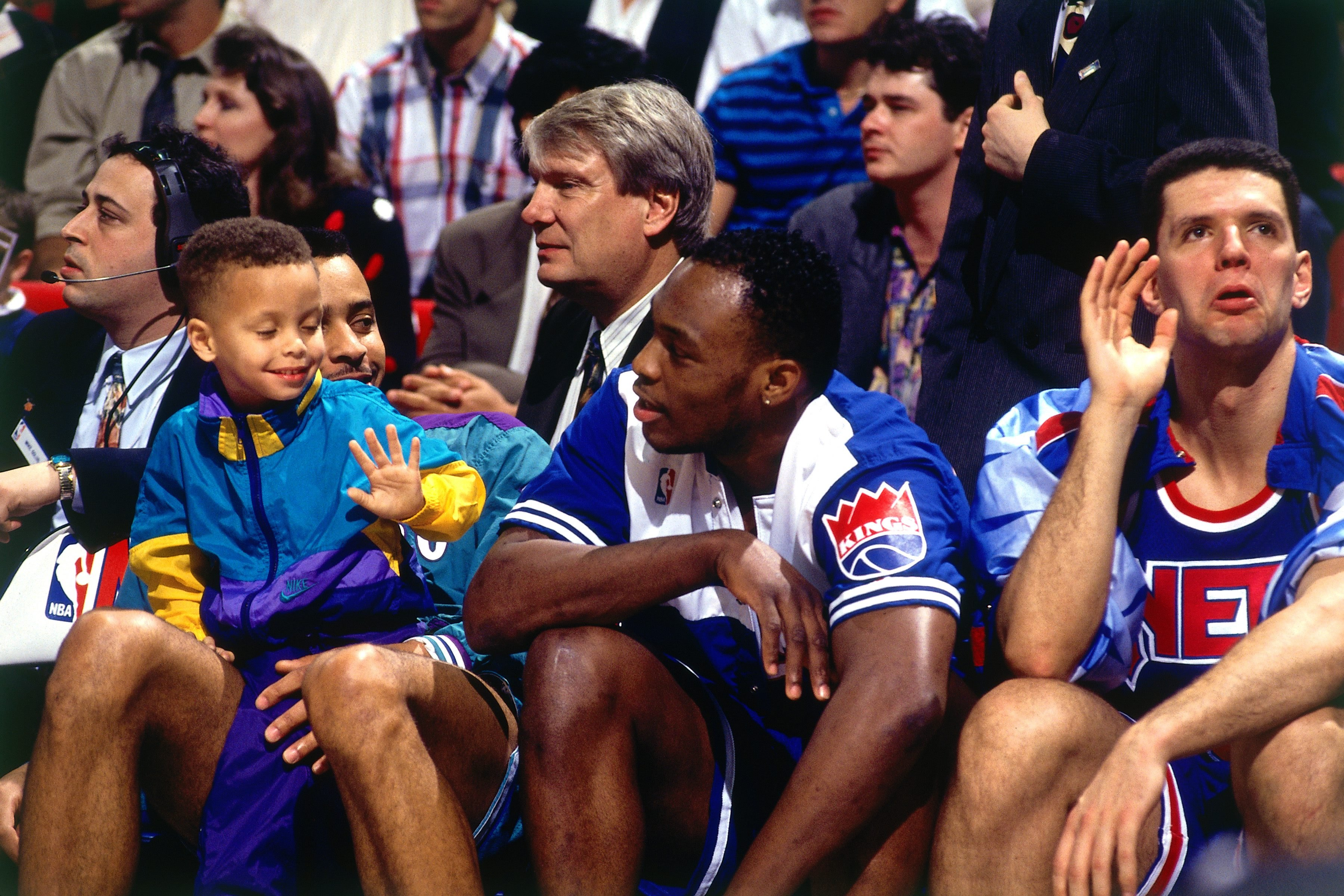 ORLANDO - FEBRUARY 8:  (L) Dell Curry #30 of the Charlotte Hornets and his son Stephen Curry sit with Mitch Richmond #2 of the Sacramento Kings and Drazen Petrovic #3 of the New Jersey Nets during the 1992 NBA Three Point Competition on February 8, 1992 at the Orlando Arena in Orlando, Florida. NOTE TO USER: User expressly acknowledges that, by downloading and or using this photograph, User is consenting to the terms and conditions of the Getty Images License agreement. Mandatory Copyright Notice: Copyright 1992 NBAE (Photo by Andrew D. Bernstein/NBAE via Getty Images)