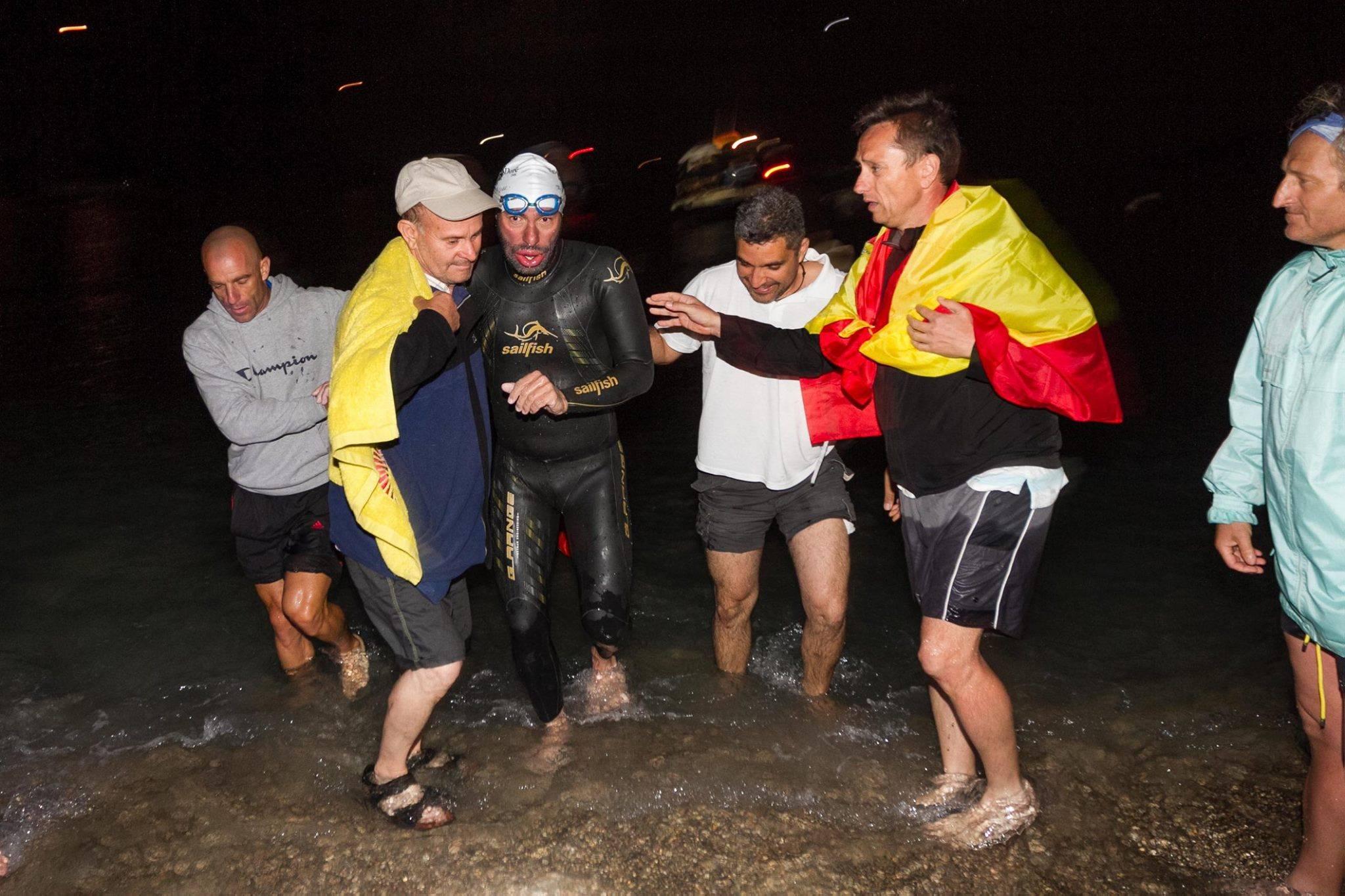 Juanjo Serra, ayudado a salir del mar en su llegada a Ibiza. / Vicent Marí
