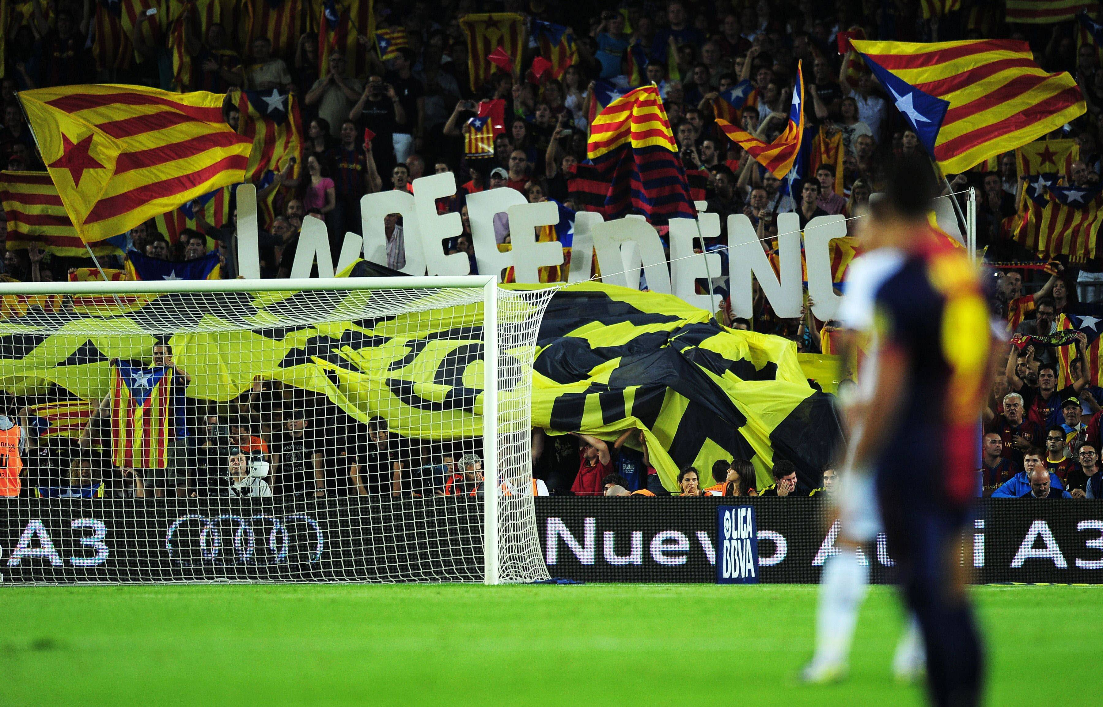 "Barcelona's football fans hold letters forming the word ""Independencia"" and wave ""Estelada"", the Catalan independentist flag, during the Spanish League Clasico football match FC Barcelona vs Real Madrid CF on October 7, 2012 at the Camp Nou stadium in Barcelona. AFP PHOTO / LLUIS GENE TELETIPOS_CORREO:SPO,SPO,%%%,%%%"